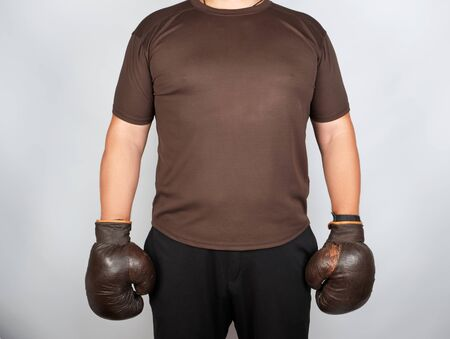 Young man stands wearing very old vintage brown boxing gloves on his hands, white background