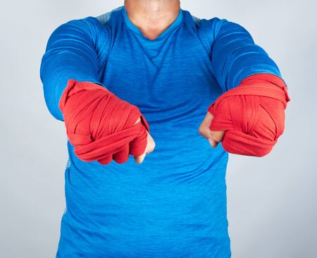 Adult athlete in blue clothes, hands wrapped in a red elastic bandage, stand before sporting events
