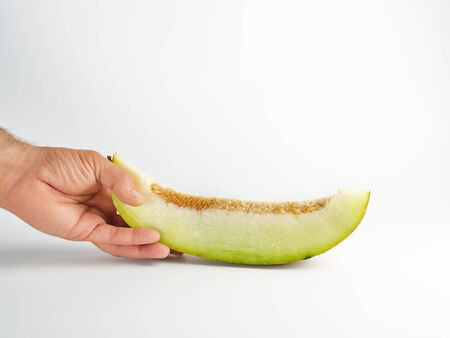 male hand holds a piece of ripe melon with seeds on a white background Standard-Bild