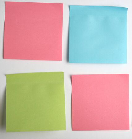 adesivi di carta rosa, blu, verde vuoti incollati su sfondo bianco, primo piano