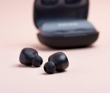 Paar schwarze kabellose kleine Ohrhörer und eine Ladebox auf beigem Hintergrund Standard-Bild