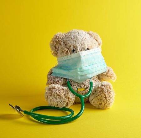 gray teddy bear and green medical stethoscope on a yellow background, treatment concept for children