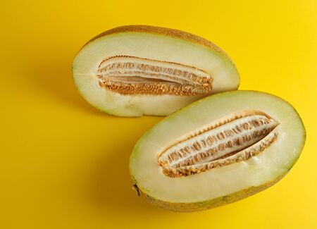 piece of ripe melon with seeds on a yellow background, summer sweet fruit