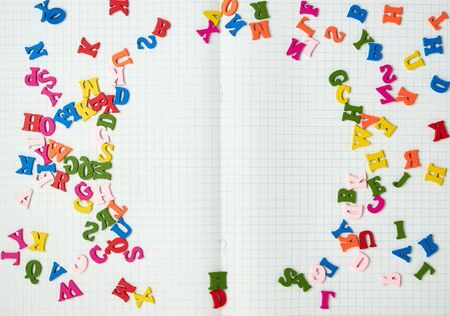 open notebook with white sheets in a box and small multi-colored wooden letters, back to school, copy space