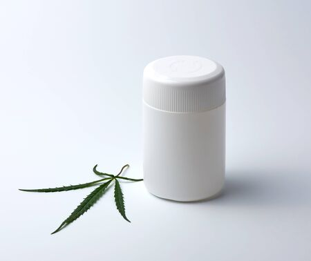 empty white plastic medical jar for pills and green hemp leaf on a white background, alternative medicine concept Stock Photo