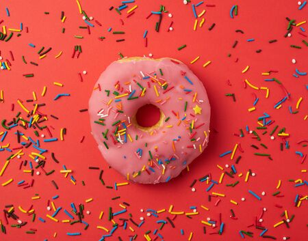 one pink round donut with colored sprinkles on a red background, top view