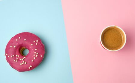 round red glazed doughnut and paper cup with coffee on a colored background, top view