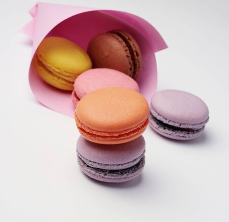multi-colored baked macaroons from almond flour on a white background, close up