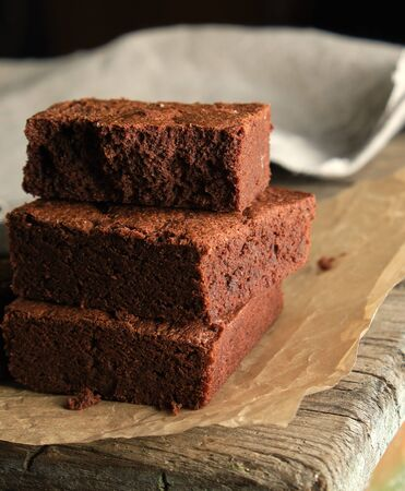 stack of baked square pieces of chocolate brownie cake on brown parchment paper, top view