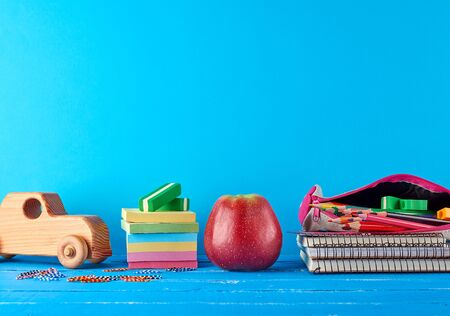 ripe red apple, stack of notebooks and multi-colored wooden pencils, children's toy car on a blue background, concept back to school