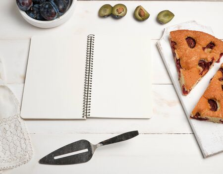open notebook with blank white pages, baked pie with plums and fresh fruits, top view, flat lay Imagens