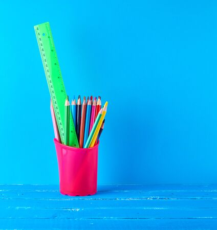 pink stationery glass with multi-colored wooden pencils and , blue background, copy space