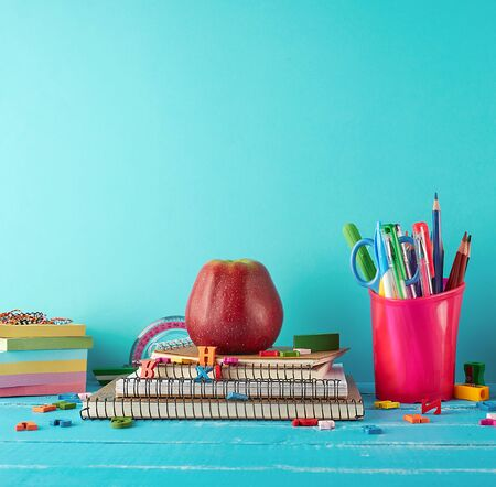 school supplies: notebook, pencils, stickers, scissors on a blue background, concept of back to school