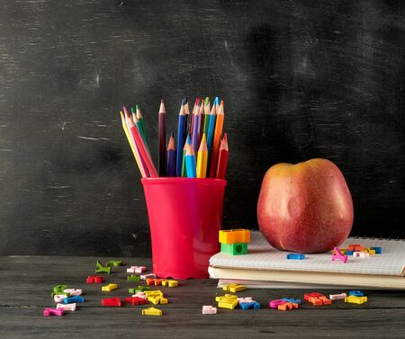 ripe red apple on a stack of notebooks,  red stationery glass with multi-colored wooden pencils  on the background of an empty black chalk board, back to school concept