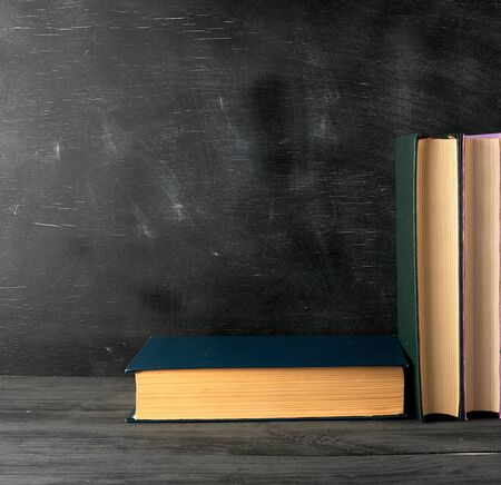 closed books with yellow sheets on a black chalk board background, copy space, back to school concept