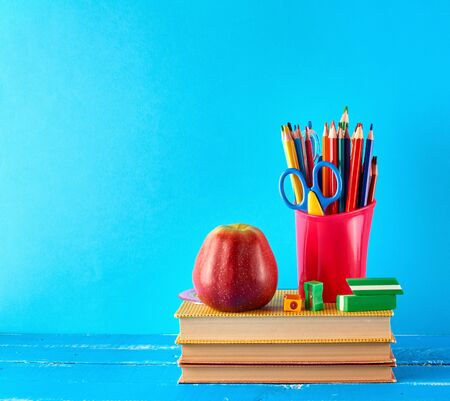 red plastic cup with multi-colored wooden pencils stands on a stack of books, ripe red apple on a blue background, concept of back to school