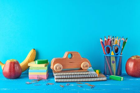 set of school supplies: notebook, pencils, stickers, paper clips, scissors and a wooden retro toy car on a blue background, concept of back to school Banco de Imagens