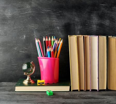 stack of books and a blue stationery glass with multi-colored wooden pencils,  on the background of an empty black chalk board, back to school concept