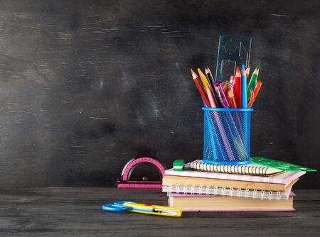stack of notebooks, blue glass with multi-colored wooden pencils and pens, rulers and an eraser on the background of an empty black chalk board, back to school concept