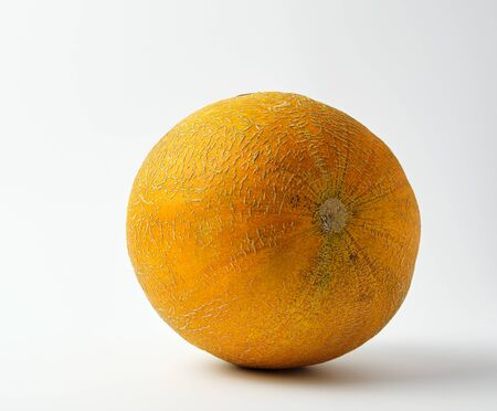 whole ripe round  yellow melon on a white background, summer fruit, close up