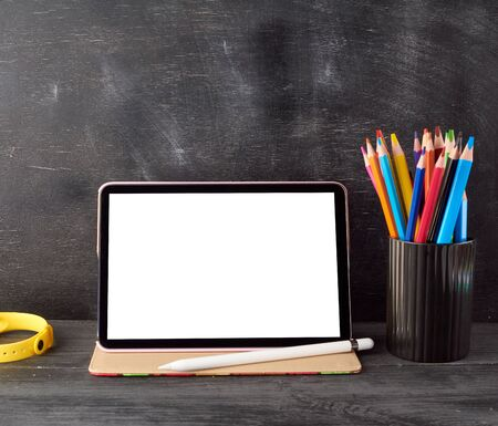 electronic tablet with a blank white screen and multi-colored wooden pencils on a black chalk board background, concept back to school