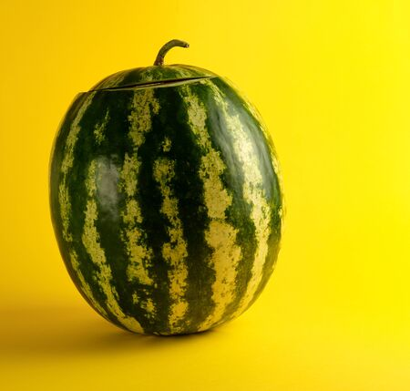 big oval green striped whole watermelon on a yellow background, summer berry Stock fotó