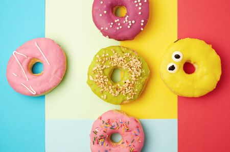 round different donuts with sprinkles on a bright multi-colored background, top view