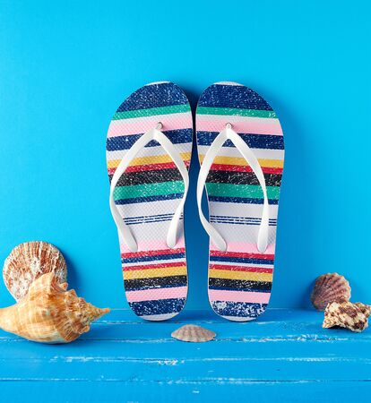 pair of multi-colored rubber slippers on a blue background, near seashells, background for travel and leisure