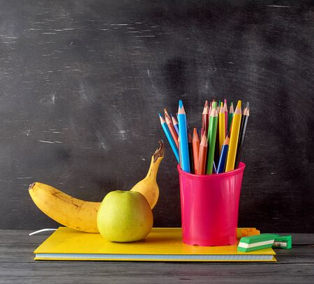 ripe green apple, banana on a stack of notebooks, red stationery glass with multi-colored wooden pencils on the background of an empty black chalk board, back to school concept
