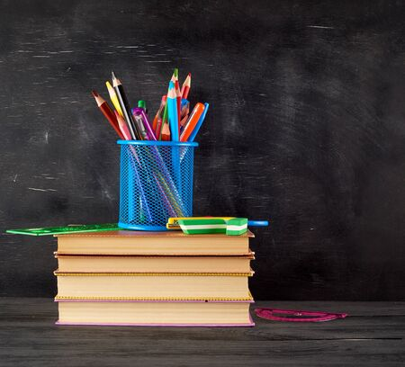 stack of books and a blue stationery glass with multi-colored wooden pencils and pens, rulers and an eraser on the background of an empty black chalk board, back to school concept