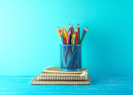 metal blue stationery stand with multi-colored wooden pencils on a blue background, concept back to school Stok Fotoğraf