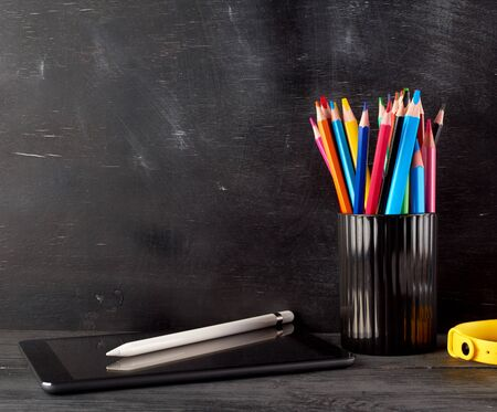 black glass with multi-colored wooden pencils, near an electronic tablet and a white pencil, black background Stok Fotoğraf