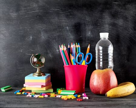 apple, banana, bottle of water and stationery for school on the background of an empty black chalk board, copy space, back to school concept 版權商用圖片