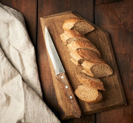 sliced rye flour baguette on a wooden cutting board, top view