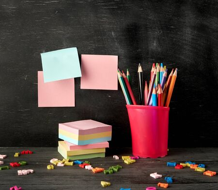 red plastic glass with colorful wooden pencils,  stack of paper color stickers, black chalkboard background, copy space 版權商用圖片