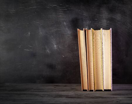 four closed books with yellow sheets on a black chalk board background, copy space, back to school concept