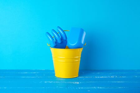 yellow childrens metal bucket and plastic shovel and rake on a blue background, concept of sea holidays