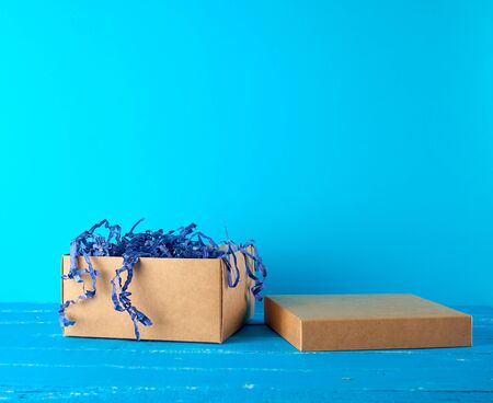 open empty brown craft box on a blue wooden background, holiday backdrop