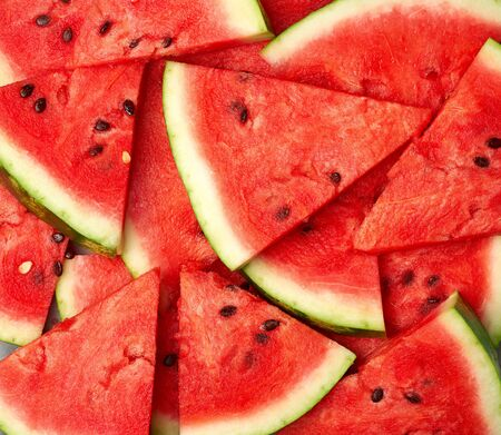 sliced triangular slices of ripe red watermelon with brown seeds, bright summer texture backdrop