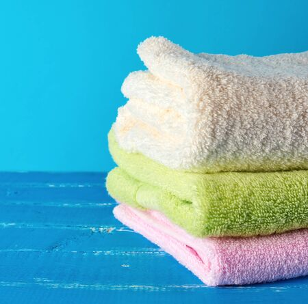 stack of multi-colored new terry bath towels on a blue wooden background , copy space Zdjęcie Seryjne