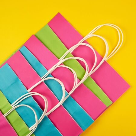 multi-colored paper shopping bags with white handles on a yellow background, flat lay