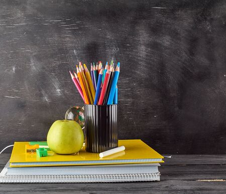 ripe green apple on a stack of notebooks, black stationery glass with multi-colored wooden pencils on the background of an empty black chalk board, back to school concept