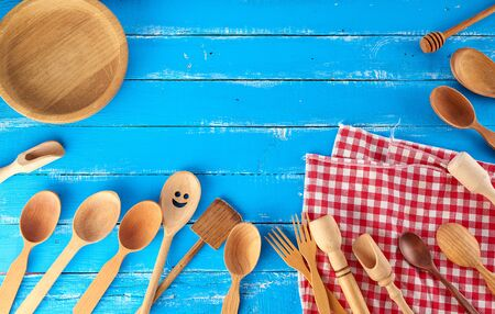 many different wooden spoons, forks and empty plate on a blue background, copy space, kitchen backdrop