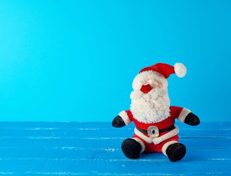 toy Santa Claus in a red suit sitting on a blue background, christmas backdrop
