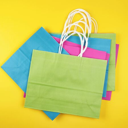 stack rectangular multi-colored paper shopping bags with white handles on a yellow background, flat lay