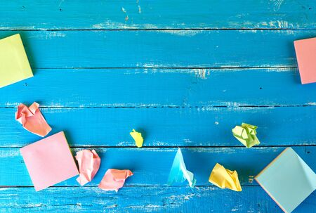 multicolored empty paper square stickers on blue wooden background, copy space 免版税图像