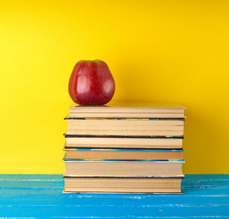 red ripe apple lies on a stack of books, yellow background, back to school, fruit