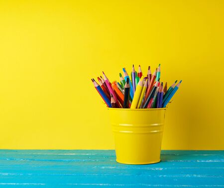 yellow green bucket with multi-colored wooden pencils and pens on a blue wooden table, concept back to school, copy space