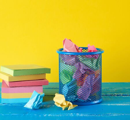 blue metal bucket filled with crumpled multi-colored white paper, yellow  background, business concept