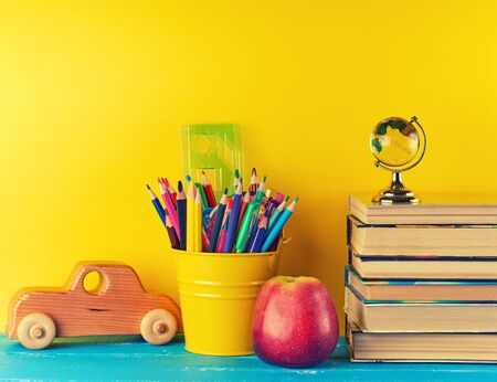 background back to school with childrens stationery pencils, books, apple, glass globe on a blue background 版權商用圖片